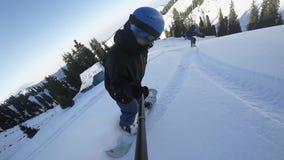 Ciérrese para arriba de los snowboarders extremos que montan por el polvo por GoPro metrajes
