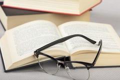 Ciérrese para arriba de los vidrios de lectura que ponen en un libro Imágenes de archivo libres de regalías