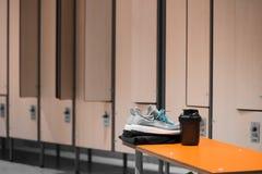 Ciérrese para arriba de los zapatos de los deportes, de la ropa de deportes y de la botella de agua del deporte en vestuario del  fotografía de archivo