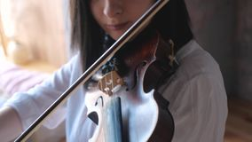 Ciérrese para arriba de músico de la mujer en la camisa blanca que toca el violín almacen de video