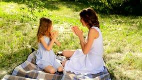 Ciérrese para arriba de mamá joven atractiva y su de la hija linda que juegan al juego que aplaude almacen de metraje de vídeo