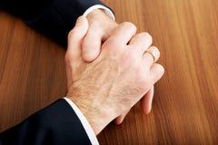 Ciérrese para arriba de manos apretadas hombre de negocios en el escritorio Foto de archivo libre de regalías