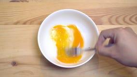 Ciérrese para arriba de manos baten el huevo en un cuenco blanco para preparar la tortilla metrajes