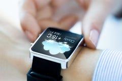 Ciérrese para arriba de manos con el icono del tiempo en smartwatch Fotos de archivo