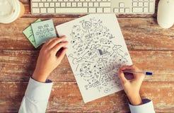 Ciérrese para arriba de manos con esquema del dibujo en el papel Imagenes de archivo