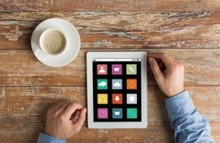 Ciérrese para arriba de manos con los iconos del menú en la PC de la tableta Imágenes de archivo libres de regalías
