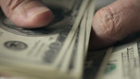 Ciérrese para arriba de manos de un viejo hombre que cuenta cientos billetes de dólar en una tabla almacen de metraje de vídeo