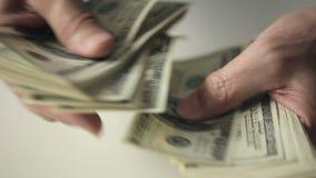 Ciérrese para arriba de manos de un viejo hombre que cuenta cientos billetes de dólar en una tabla almacen de video