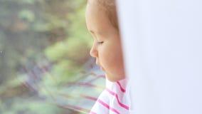 Ciérrese para arriba de manos en las rodillas de la niña linda que se sientan en el alféizar de la ventana metrajes