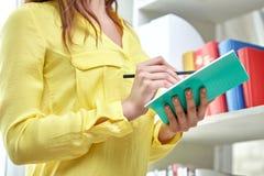 Ciérrese para arriba de manos femeninas con el cuaderno y el lápiz Imagen de archivo