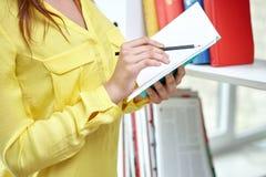 Ciérrese para arriba de manos femeninas con el cuaderno y el lápiz Imágenes de archivo libres de regalías