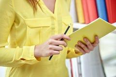 Ciérrese para arriba de manos femeninas con el cuaderno y el lápiz Imagen de archivo libre de regalías