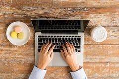 Ciérrese para arriba de manos femeninas con el ordenador portátil y el café Imagenes de archivo