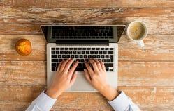Ciérrese para arriba de manos femeninas con el ordenador portátil y el café Imagen de archivo