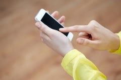 Ciérrese para arriba de manos femeninas con smartphone en casa Foto de archivo