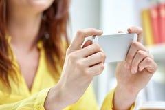 Ciérrese para arriba de manos femeninas con smartphone en casa Imagen de archivo