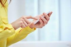 Ciérrese para arriba de manos femeninas con smartphone en casa Fotos de archivo