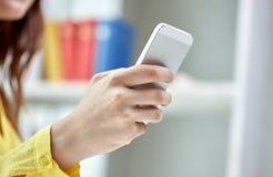 Ciérrese para arriba de manos femeninas con smartphone en casa Fotografía de archivo libre de regalías