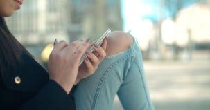 Ciérrese para arriba de manos femeninas jovenes usando el teléfono, al aire libre Imagen de archivo