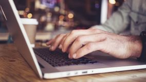 Ciérrese para arriba de manos usando el ordenador portátil en la tabla almacen de metraje de vídeo