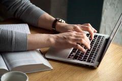 Ciérrese para arriba de mecanografiar masculino en el ordenador portátil que estudia en café fotos de archivo