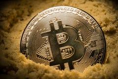 Ciérrese para arriba de mitad del bitcoin en la arena Foto de archivo libre de regalías