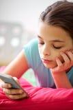 Ciérrese para arriba de muchacha aburrida con smartphone en casa Fotos de archivo