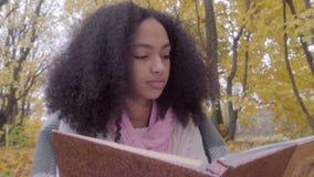 Ciérrese para arriba de muchacha adolescente negra linda con el álbum del dibujo en bosque del otoño almacen de metraje de vídeo