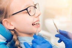 Ciérrese para arriba de muchacha asustada con los apoyos que asisten al dentista Fotos de archivo libres de regalías