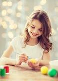 Ciérrese para arriba de muchacha con el cepillo que colorea los huevos de Pascua Fotografía de archivo libre de regalías