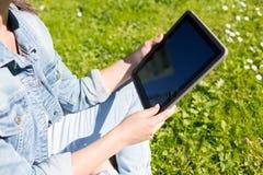 Ciérrese para arriba de muchacha con la PC de la tableta que se sienta en hierba Fotografía de archivo