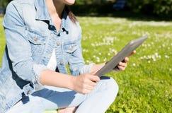 Ciérrese para arriba de muchacha con la PC de la tableta que se sienta en hierba Foto de archivo libre de regalías