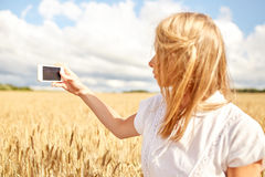 Ciérrese para arriba de muchacha con smartphone en campo de cereal Imagenes de archivo