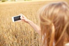 Ciérrese para arriba de muchacha con smartphone en campo de cereal Fotografía de archivo libre de regalías