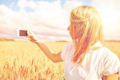 Ciérrese para arriba de muchacha con smartphone en campo de cereal Fotografía de archivo