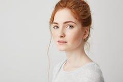 Ciérrese para arriba de muchacha hermosa blanda joven del jengibre con los ojos azules que miran la cámara sobre el fondo blanco  Fotografía de archivo