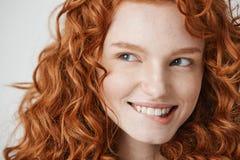 Ciérrese para arriba de muchacha hermosa con el pelo rojo rizado y el labio penetrante sonriente de las pecas sobre el fondo blan Fotografía de archivo libre de regalías