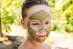 Ciérrese para arriba de muchacha hermosa con la máscara facial del pepino Foto de archivo