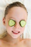 Ciérrese para arriba de muchacha hermosa con la máscara facial del pepino Foto de archivo libre de regalías