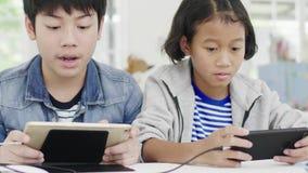 Ciérrese para arriba de muchacha linda asiática y del muchacho joven que juegan en videojuego competitivo en smartphones almacen de video