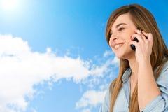 Ciérrese para arriba de muchacha linda en el teléfono celular al aire libre. Imagen de archivo