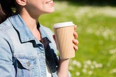 Ciérrese para arriba de muchacha sonriente con la taza de café al aire libre Imágenes de archivo libres de regalías
