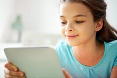 Ciérrese para arriba de muchacha sonriente con PC de la tableta en casa Fotografía de archivo