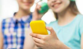 Ciérrese para arriba de muchachas con smartphone y los auriculares Foto de archivo libre de regalías