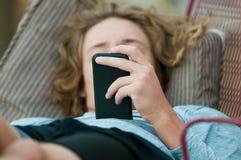 Ciérrese para arriba de muchacho adolescente en el teléfono celular Foto de archivo libre de regalías