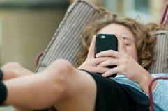 Ciérrese para arriba de muchacho adolescente en el teléfono celular Imágenes de archivo libres de regalías