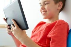 Ciérrese para arriba de muchacho con el ordenador de la PC de la tableta en casa Foto de archivo libre de regalías