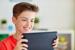 Ciérrese para arriba de muchacho con el ordenador de la PC de la tableta en casa Fotos de archivo
