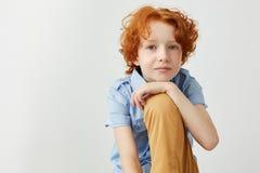 Ciérrese para arriba de muchacho hermoso del jengibre en camisa azul y los vaqueros amarillos que llevan a cabo la mano en la pie Fotos de archivo