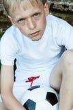 Ciérrese para arriba de muchacho rubio y azul observado con la bola Fotos de archivo libres de regalías